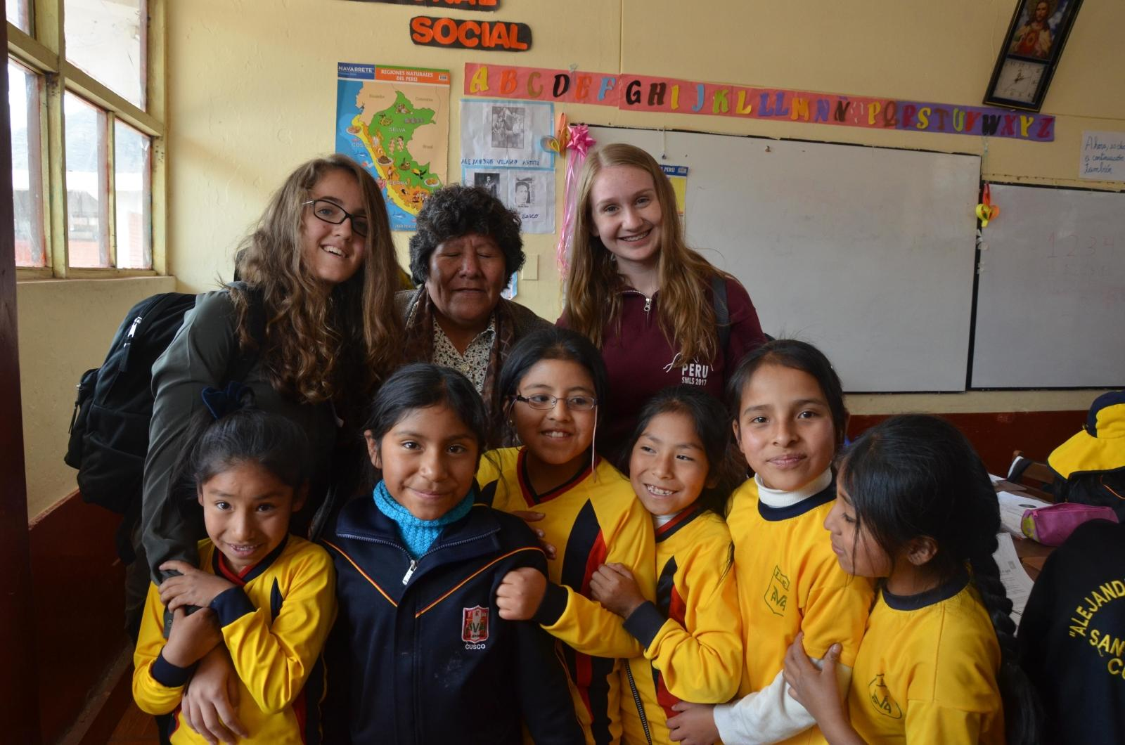 Projects Abroad volunteers posing with kids and their teacher at school during their spring break in Peru.